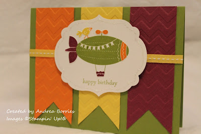 "Green card with three banners (orange, yellow and purple) ebossed with chevrons. Focal image is a bird walking on a blimp with the saying ""happy birthday."""