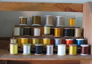 Fly tying thread displayed on racks, four levels high and 5 to 7 spools wide