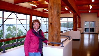 Liz in the art exhibit with large window to the lake