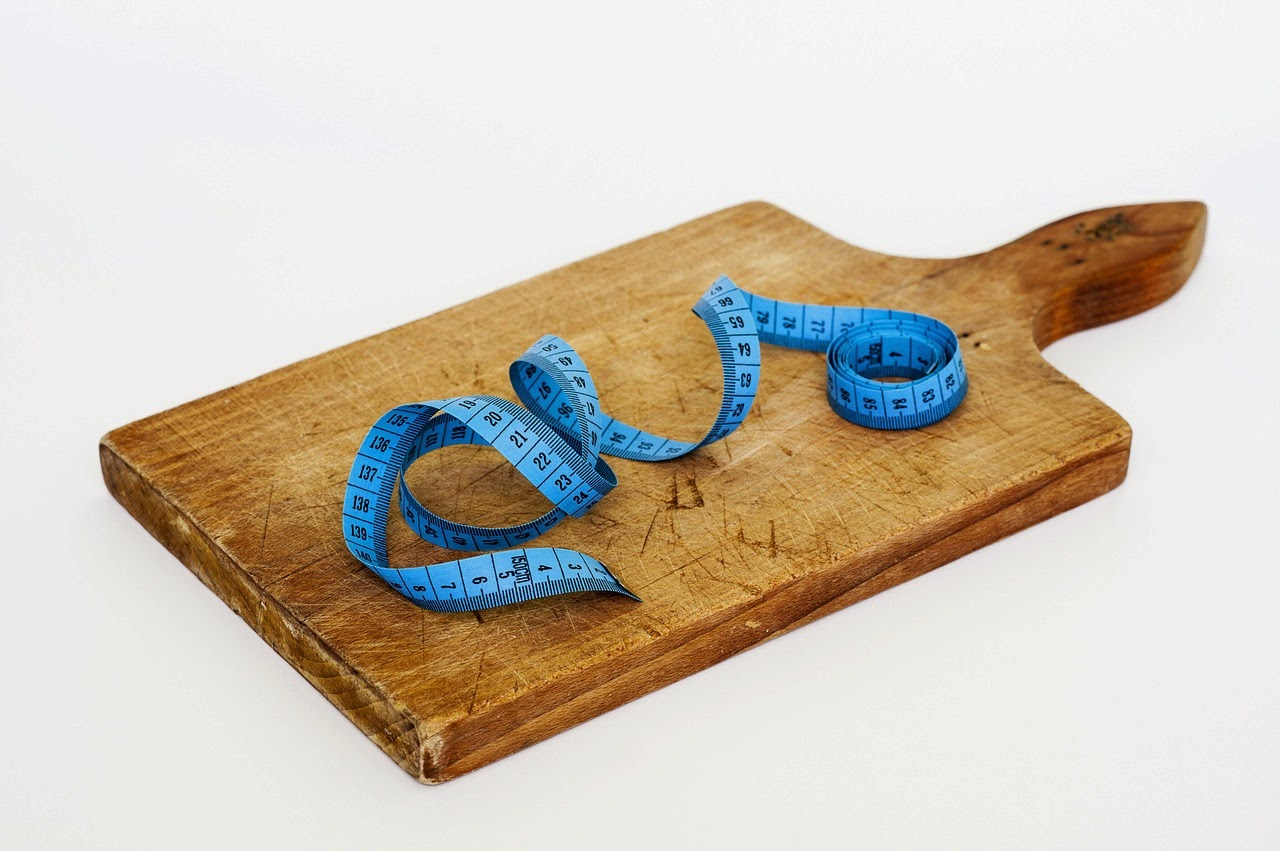 Blue tape measure and wood cutting board