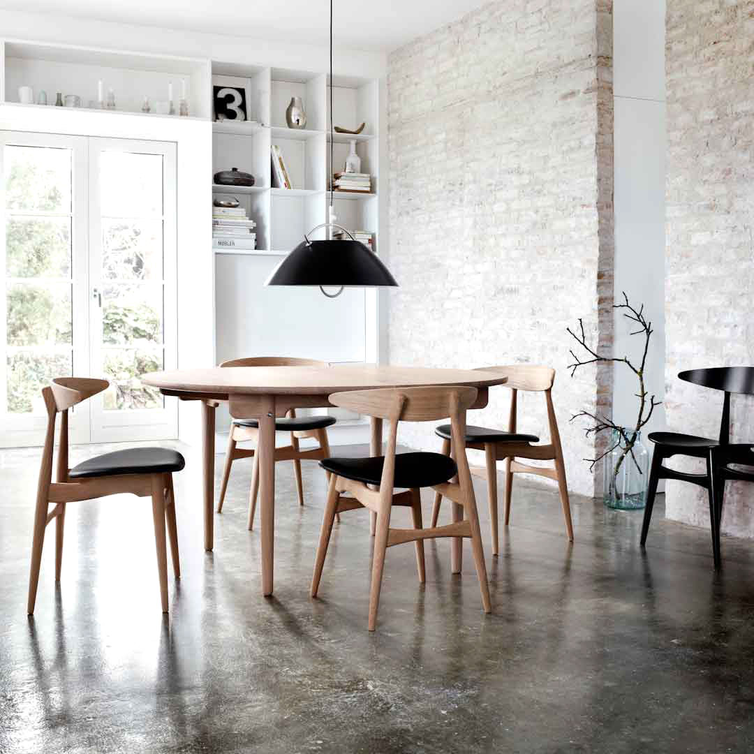 Dining room with concrete floor and wishbone chairs
