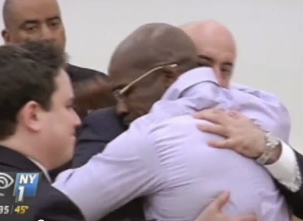 Jonathan Fleming hugs his lawyers. (Screen capture from YouTube video)