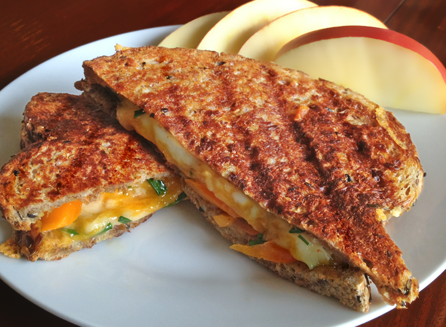 A grilled cheese sandwich, cut to show the cheese and served on a plate with apple slices.