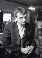 Mark E Smith in black and white leaning on a bar