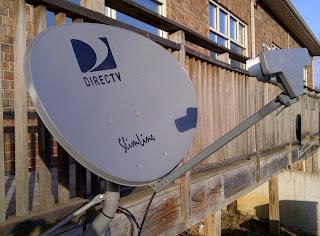 DirecTV satellite dish installed on wood deck