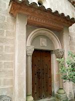 L'accés principal a la capella en la que s'aprecien els capitells i l'escut nobiliari de la família Bussanya