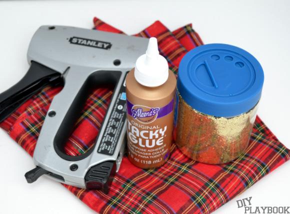 Assemble your supplies for the gold glitter reindeer wall art: canvas, fabric, staple gun, fabric glue, foam brush, reindeer silhouette, gold glitter, and pencil.