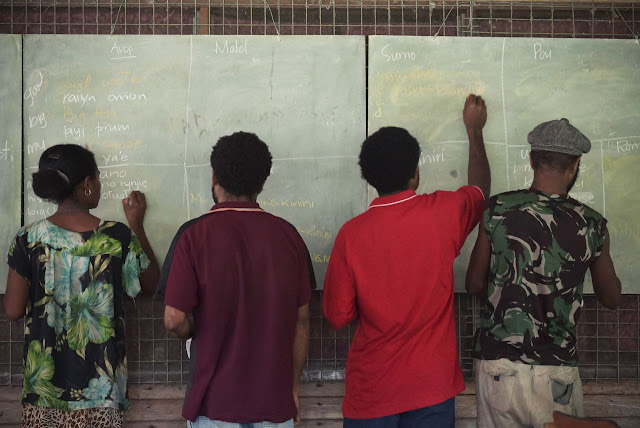 Four Papua New Guineans stand at a chalkboard working on a multi-language dictionary.