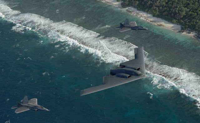 Two F-22 Raptors and a B-2 Spirit bomber deployed to Andersen Air Force Base, Guam, fly in formation over the Pacific Ocean