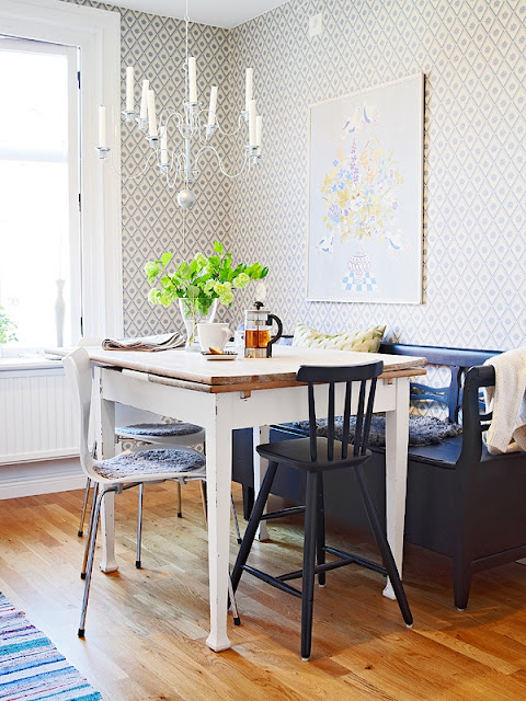 Kitchen in a small apartment with a chandelier, geometric wallpaper, blue bench, high table with mismatched chairs and a wood floor