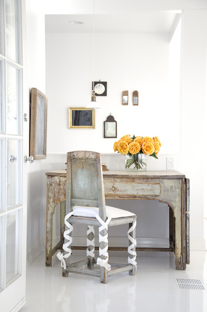 home office with reclaimed wood desk and chair with an orange flower arrangement in a glass vase