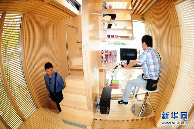 Interior of the sustainable micro house with two people walking around