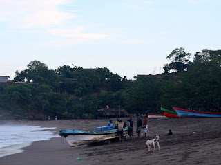 Two long boats with people surrounding them on the beach.