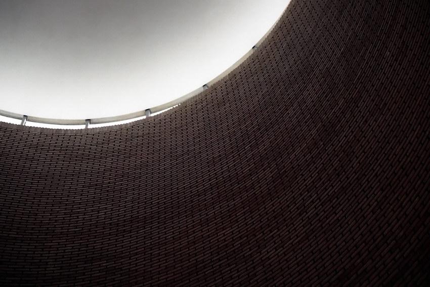Foto sobre a parede circular em tijolo maciço e as entradas de luz no tecto