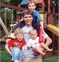Randy with his three sons in front of a swing set