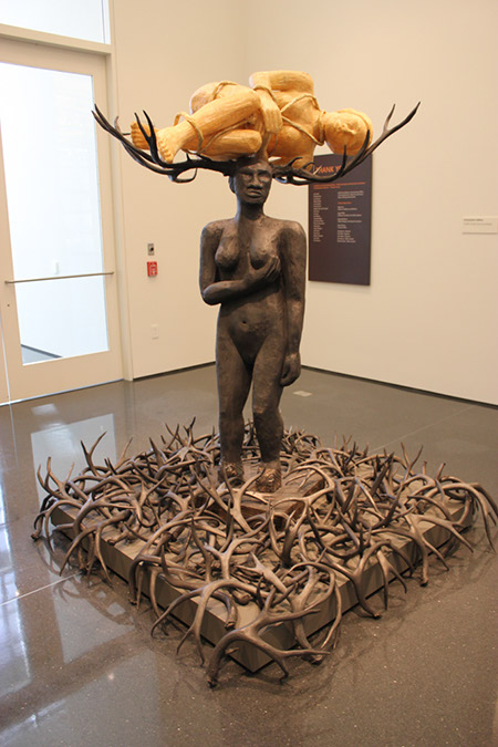 Alison Saar metal sculpture of a woman nude, with antlers carrying another woman curled in the fetal position bound.  Antlers are all around the standing figures feet.  She holds her left breast with her right hand.