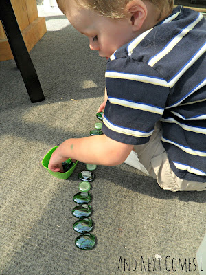 J lining up green stones from And Next Comes L