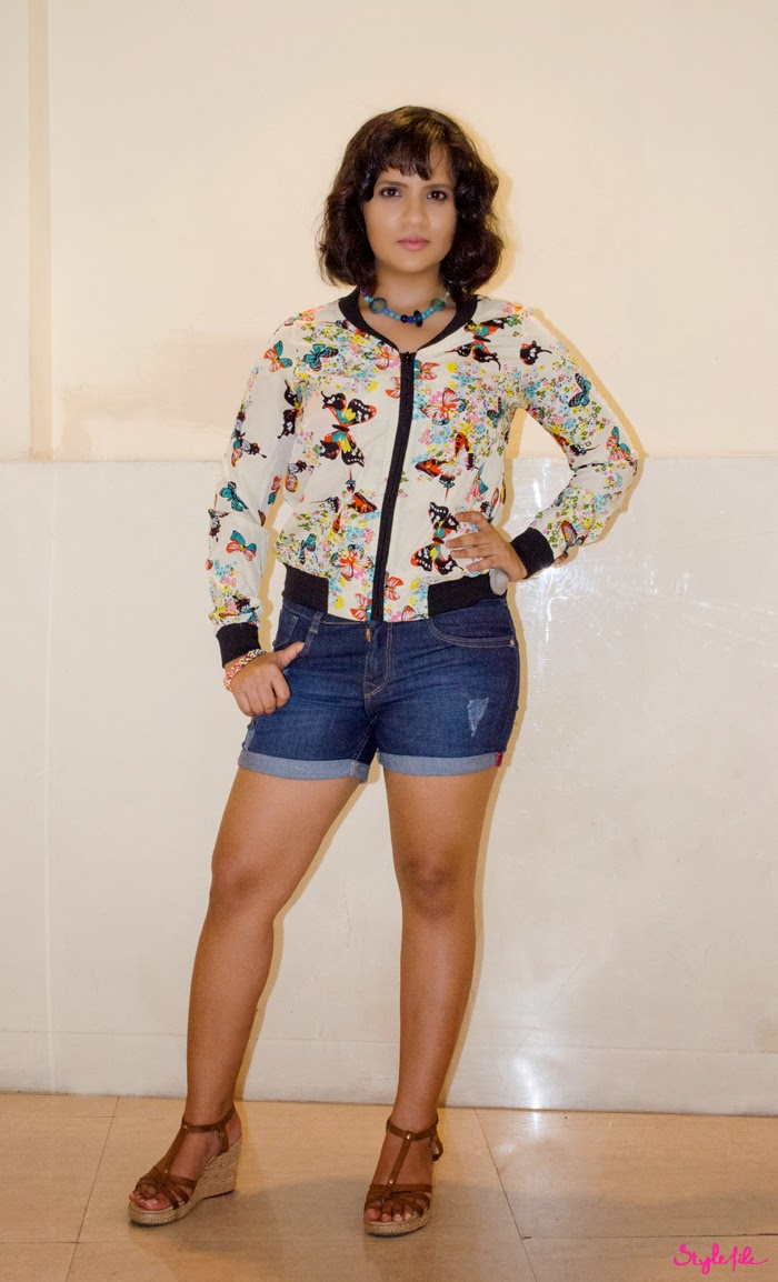 Dayle Pereira, blogger of Style File India styles a floral and tropical bomber jacket with distressed denim shorts from Reliance Trends along with wedges, a DIY necklace and a wavy bob