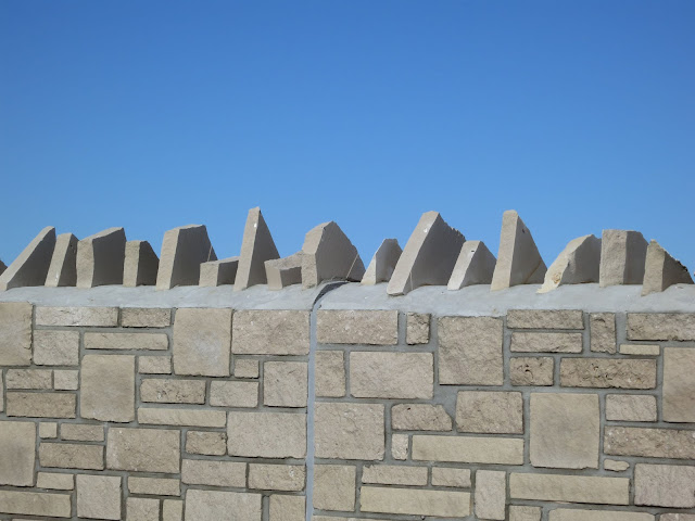 Top of a concrete and stone wall against a blue sky