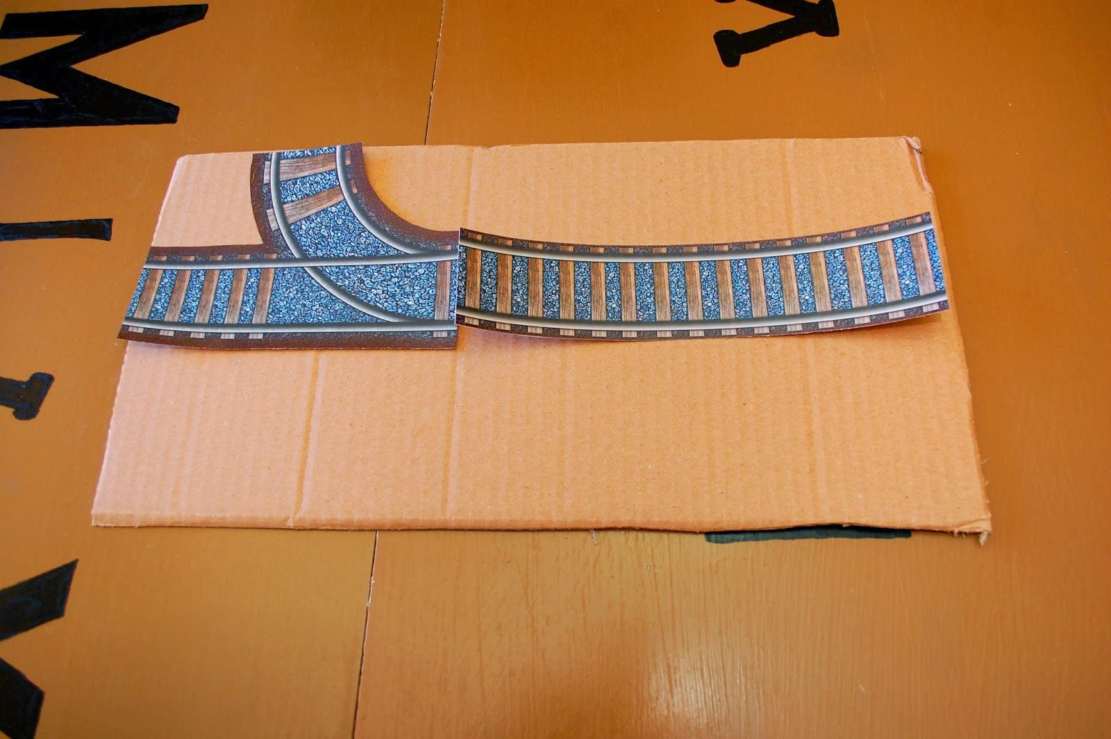 paper train tracks laid out on cardboard panel