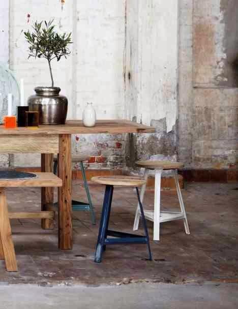 Metalowe taborety, drewniany stół, industrialne wnętrze
