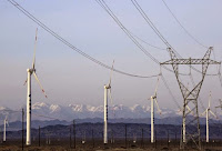 An electricity pylon is seen next to wind turbines at a wind power plant in Hami, Xinjiang Uighur Autonomous Region, China, March 21, 2015. (Credit: Reuters/Stringer) Click to Enlarge.