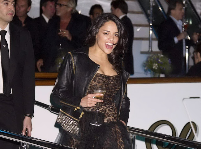 Michelle Rodriguez leaving a yacht with a glass of wine