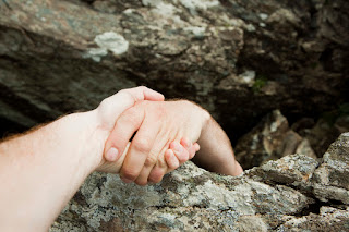 Photo of pair of hands pulling another paid of hands over a precipice.