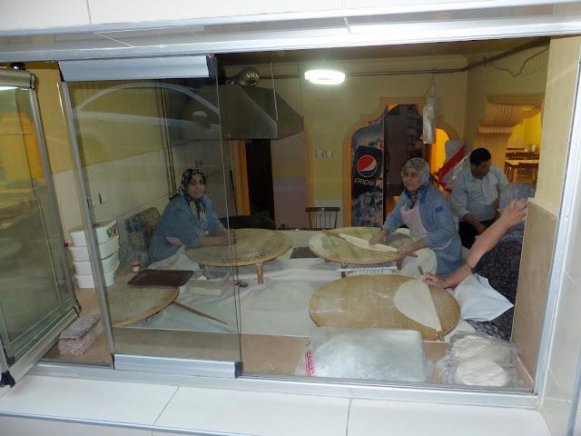 Турчанки раскатывают лепешки теста для изготовления гёзлеме
