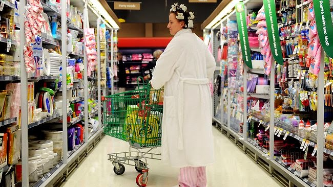 Woman in public shopping in pajamas and curlers