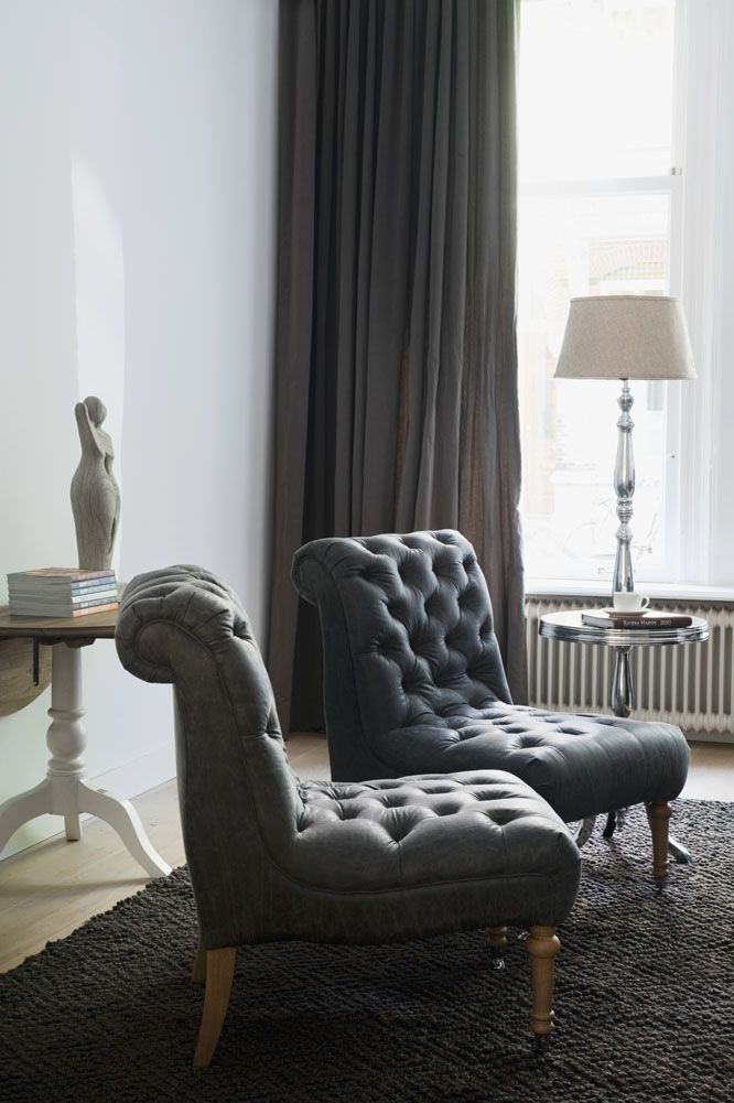 living room with gray slipper chairs and drapery