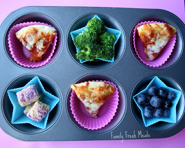 "Muffin Meals: Blueberries & Pizza For this muffin meal, there are mini slices of homemade pizza, steamed broccoli, blueberries and blueberry wheat bundles.: Big D actually created this meal. I asked her to think up the perfect lunch. I was so happy I had everything she had envisioned (except for pepperoni for our mini pizzas). She was sooooo happy when I brought out this lunch. "" MOM!!! This is everything I LOVE!!"" As you can see from the picture, I don't think she could smile any harder :)"