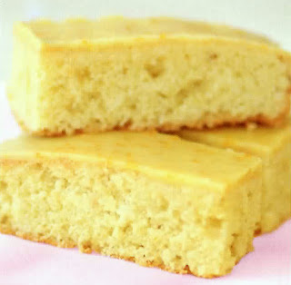 coconut and orange cake: Slices of a coconut and orange cake traybake with an orange icing piled up to serve