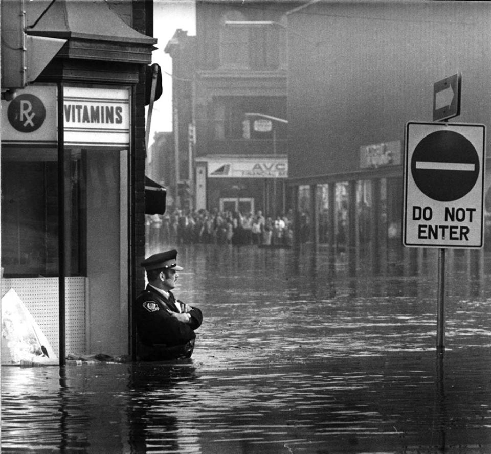 40 Amazing Historical Pictures - Police officer guarding a pharmacy in high-flood waters, Ontario, 1974