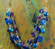 Beaded necklace has 3 strands of mingling blue and purple beads and buttons in shimmering loose twist style