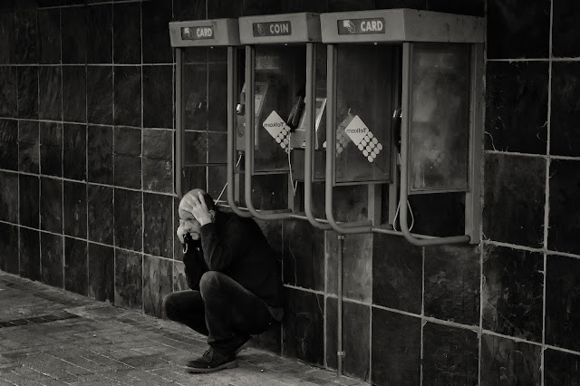 A man crouches next to a bank of telephone booths in this Cape Town street photograph
