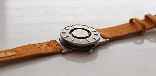 Foto der taktilen Uhr: Edelstahl Gehäuse mit edlen erhabenen Markierungen. Der Minutenzeiger ist eine Kugel, die am Ziffernblatt im Kreis läuft, der Stundenzeiger ist eine Kugel, die entlang des äußeren Randes läuft.
