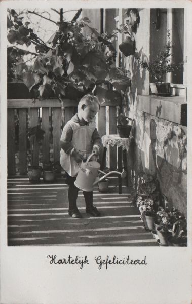 small boy in pinafore watering flowerpots with a watering can