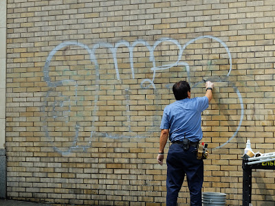 a member of building maintenance removing graffiti on the side of Hotel Max in downtown