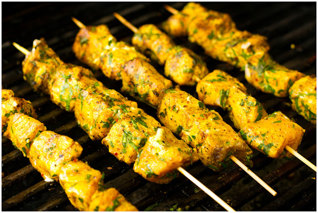 A photograph of Fish kebabs cooking on a barbecue