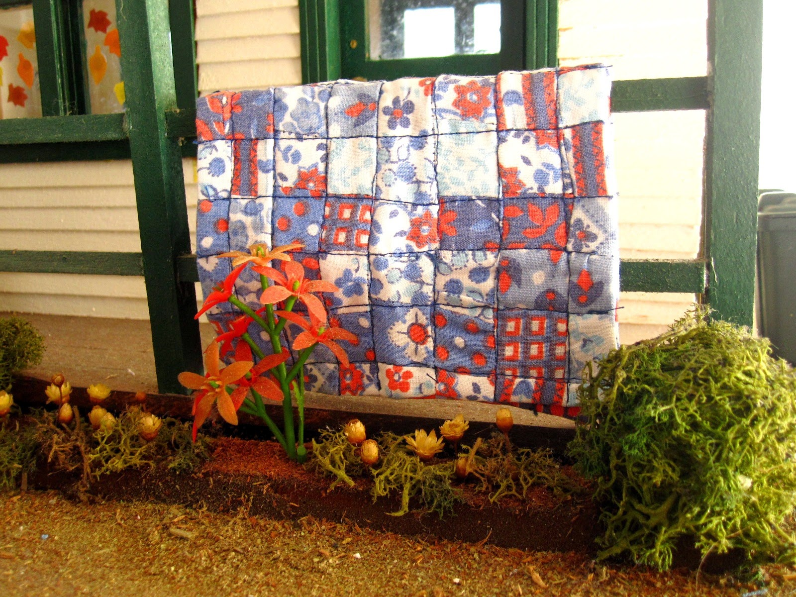 Vintage miniature quilt displayed over the front porch railing of a miniature school building.