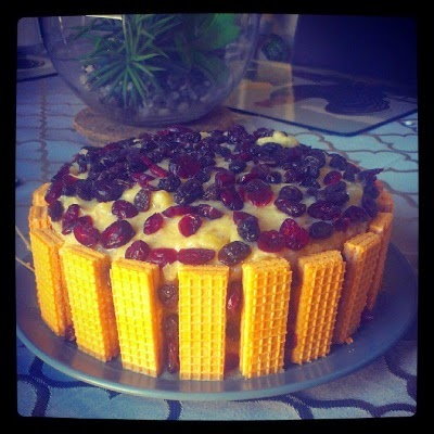 A two-layer cake edged with vanilla wafers and topped with dried cranberries and raisins atop a yellow pineapple icing.