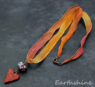 http://earthshine.indiemade.com/product/orangerust-ceramic-heart-lampwork-and-silk-ribbon-necklace