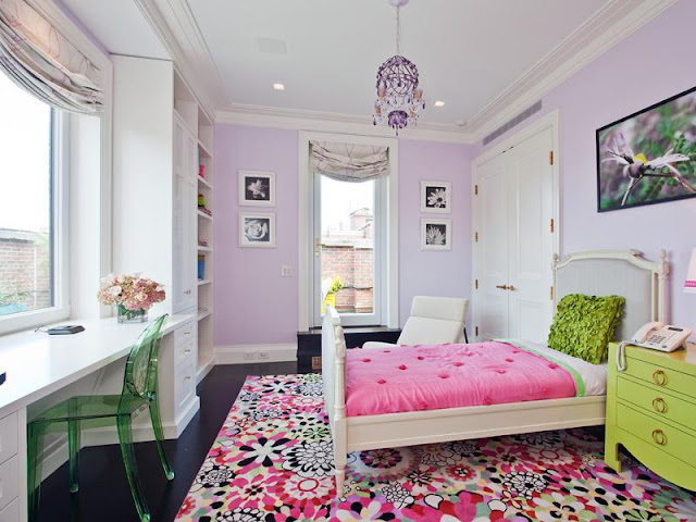 Colorful kids room in an apartment with lavender walls, a colorful rug, a chartreuse green set of drawers re purposed as a side table, a green Lucite plastic chair at a white desk with a large window, white built in bookcases and a walk in closet