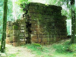 Ruínas da antiga igreja de Nuestra Señora de Loreto vistas entre duas árvores. As pedras são numeradas.