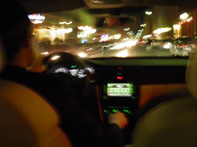Blick von der Rückbank auf den Fahrer: Alles ist unscharf, die Lichter auf der Straße zeichnen Linien.
