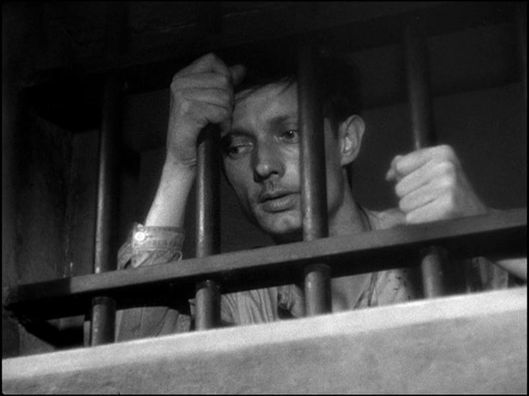 Filmstill aus dem Film 'Ein zum Tode Verurteilter ist geflohen' von Robert Bresson; die Hauptfigur Fontaine sieht aus dem vergitterten Fenster