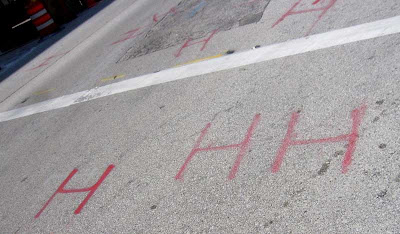 Red spray-painted shapes on asphalt look like H H H