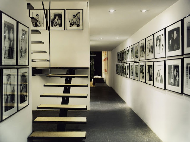 Photo of hallway with black and white minimalist staircase and lots of black and white photos on the walls