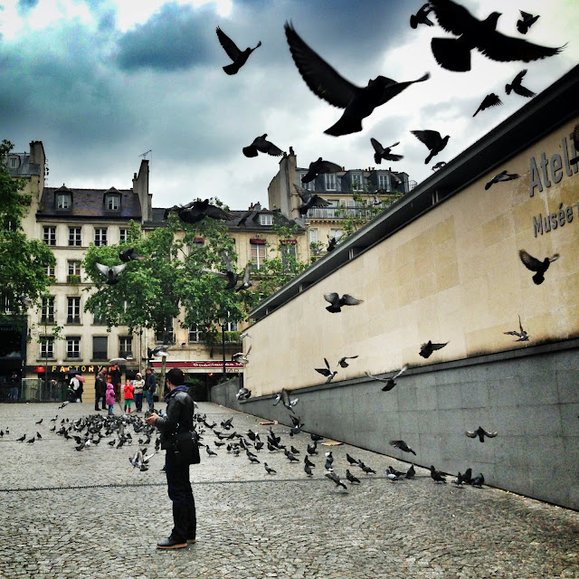 Feeding pigeons outside the Pompidou Center Paris France